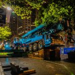 Omega Morgan large mobile crane on angle blocks crowded under tree branches on a road on downtown Seattle Washington at night