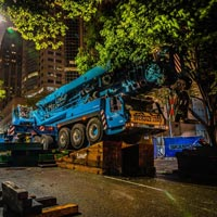 selected thumbnail button of Omega Morgan large mobile crane on angle blocks crowded under tree branches on a road on downtown Seattle Washington at night