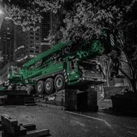deselected thumbnail button of Omega Morgan large mobile crane on angle blocks crowded under tree branches on a road on downtown Seattle Washington at night