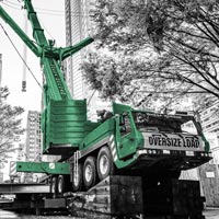 deselected thumbnail button of Omega Morgan mobile crane extended with megawing in downtown Seattle Washington, surrounded by trees and on a steep grade