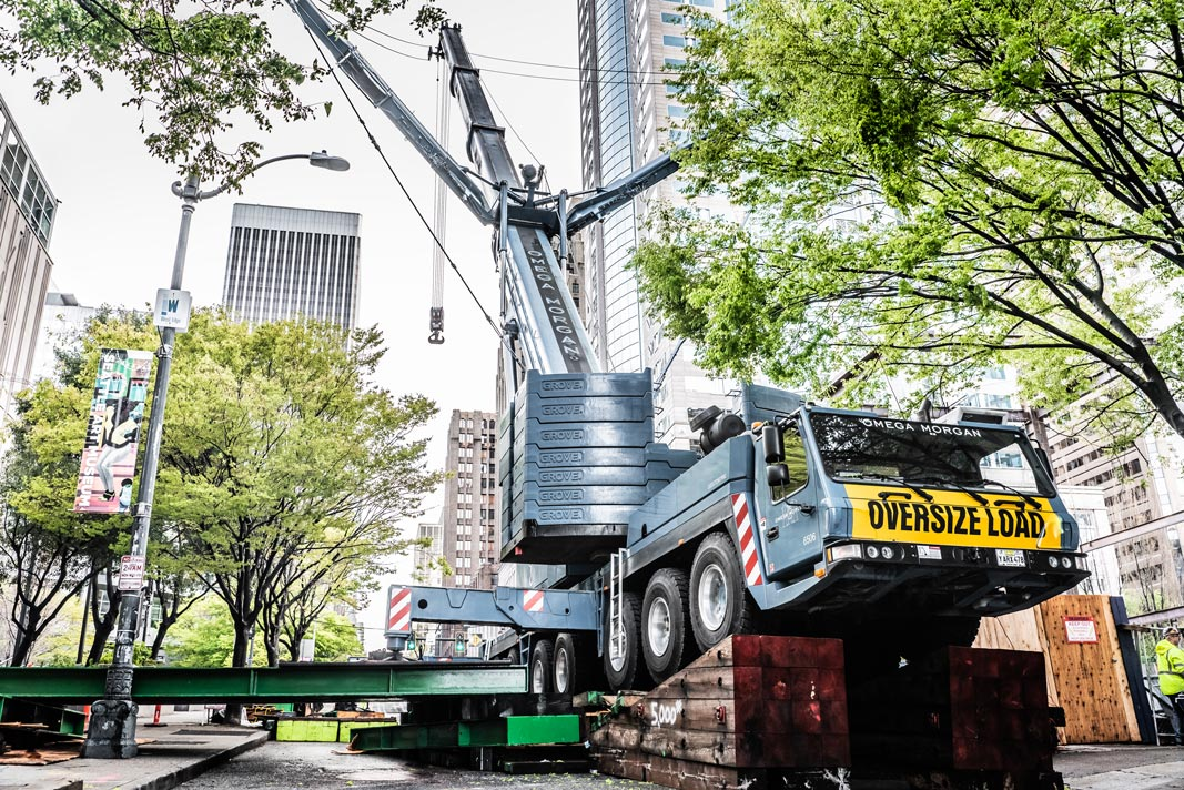 Omega Morgan mobile crane extended with megawing in downtown Seattle Washington, surrounded by trees and on a steep grade