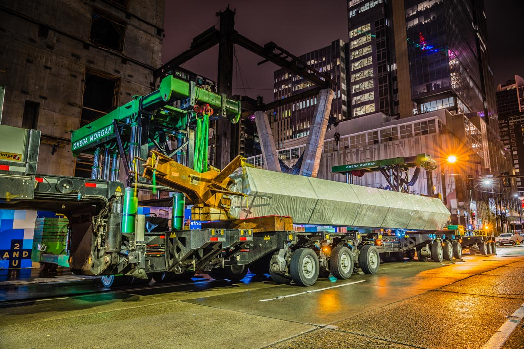 two trilifters lifting a column of of an SPMT during construction of the 2+U building construction in downtown Seattle at night