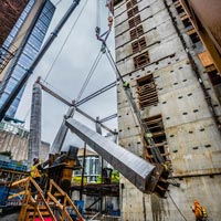 selected thumbnail button of two Omega Morgan mobile cranes lifting a column inside an under-construction skyscraper in a tight space between other buildings in downtown Seattle