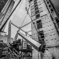 deselected thumbnail button of two Omega Morgan mobile cranes lifting a column inside an under-construction skyscraper in a tight space between other buildings in downtown Seattle