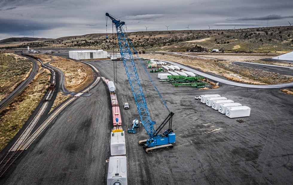 Manitowoc 14000 crawler crane offloading wind tower components from a train.