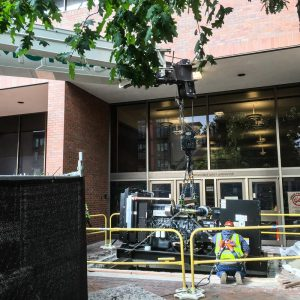 machinery moving crew member watching as a generator is lowered beneath the sidewalk at Seattle Central College