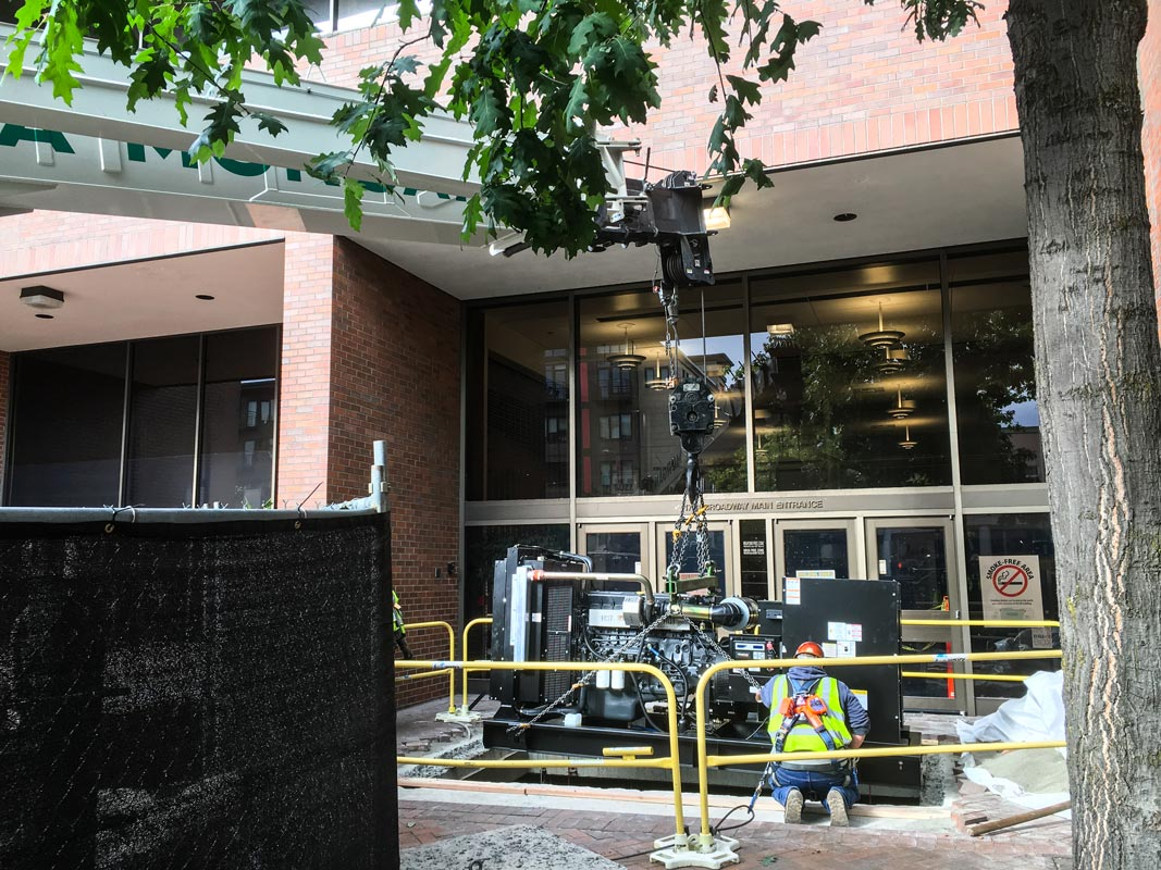 generator held by crane being lowered into an opening in the sidewalk