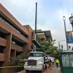 machinery moving crew using crane to lift generator into place at Seattle Central College