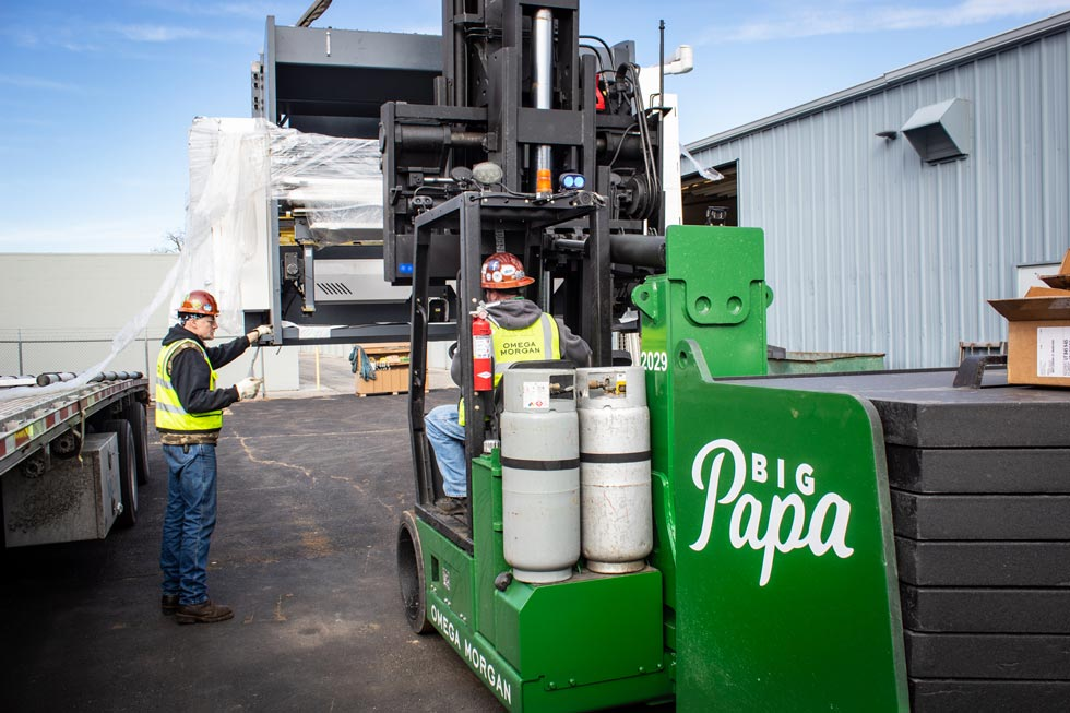 """Omega Morgan Machinery Moving team using a Hoist FR 40/60 forklift labeled """"Big Papa"""" to move metal fabrication equipment"""