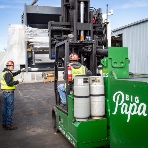 """Two Omega Morgan Machinery Moving team members use a Hoist FR 40/60 forklift labeled """"Big Papa"""" to move metal fabrication equipment"""