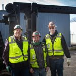 "Three Omega Morgan Machinery Moving team members smiling after using a Hoist FR 40/60 forklift named ""Big Papa"" to move metal fabrication equipment"