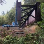 piece of a bridge in Port Angeles rainforest being lifted by Omega Morgan 500-ton Liebherr Crane