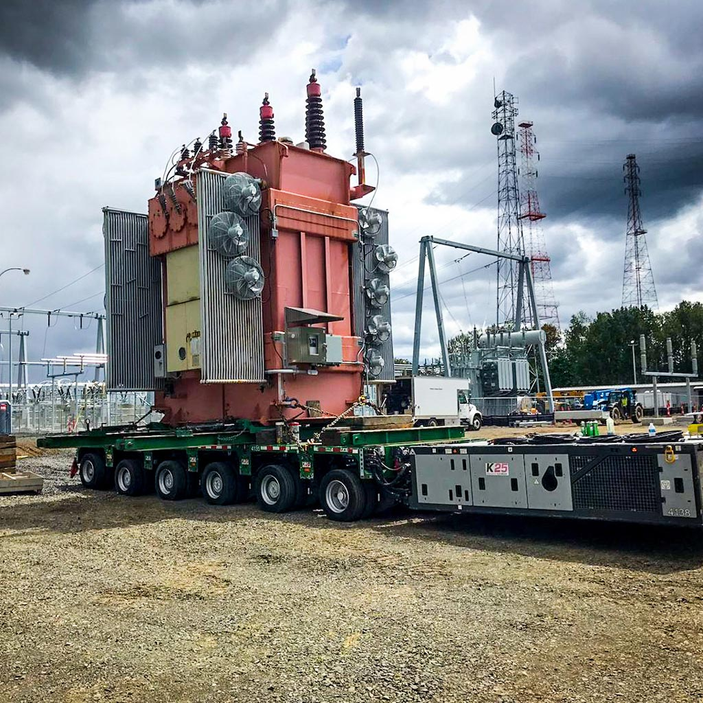 a fully-dressed transformer on top of a 6-1 line SPMT trailer in Portland at a Portland General Electric Substation in front of dark and cloudy skies