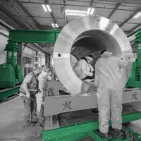 deselected button image of various workers around and inside a isostatic press that is sitting on its side waiting to be installed at Kittyhawk in Canby, Oregon