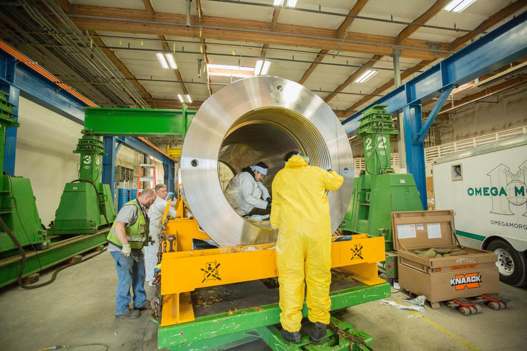 various workers around and inside a isostatic press that is sitting on its side waiting to be installed at Kittyhawk in Canby, Oregon