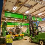 Omega Morgan crew maneuvering machinery around an isostatic press preparing to be installed