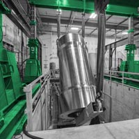 deselected button image of a large silver isostatic press held by a large gantry during the installation process