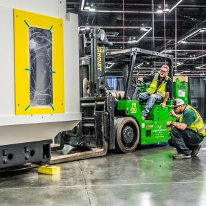 two Omega Morgan machinery moving teammembers with one on a forklift precisely moving a large piece of machinery into place at the Oregon Convention Center