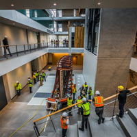 selected thumbnail button of various people watch from balcony above as omega morgan machinery moving crew move the iconic mural into the new building