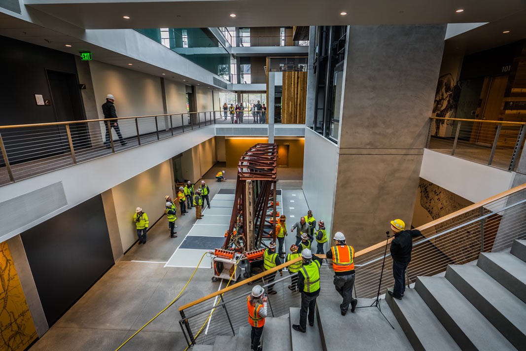 various people watch from balcony above as omega morgan machinery moving crew move the iconic mural into the new building