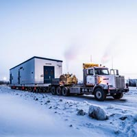 selected thumbnail button of semi truck carrying a white and blue building on a trailer across a snowy road in Calgary