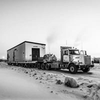 deselected thumbnail button of semi truck carrying a white and blue building on a trailer across a snowy road in Calgary