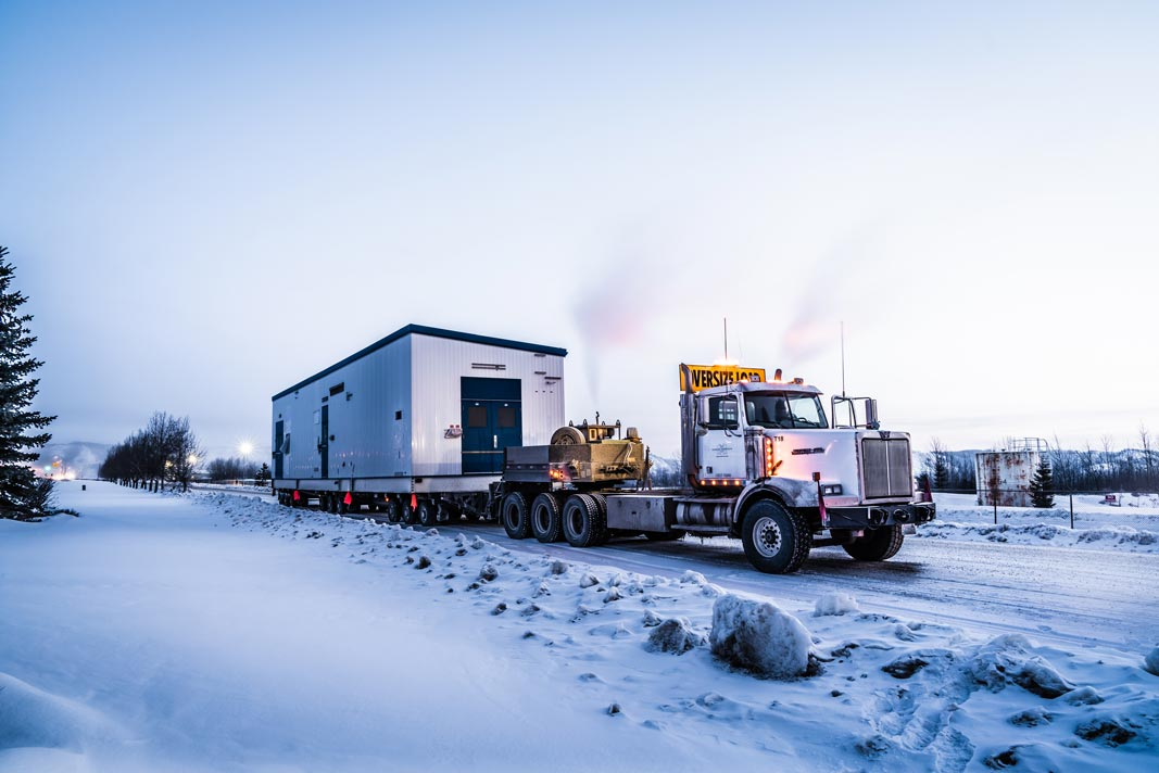 semi truck carrying a white and blue building on a trailer across a snowy road in Calgary