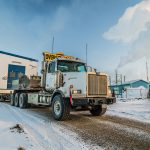 omega morgan oversize load semi truck on a snowy road in Calgary with a specialized transportation worker stands beside the road looking on