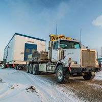 selected thumbnail button of omega morgan oversize load semi truck on a snowy road in Calgary with a specialized transportation worker stands beside the road looking on