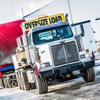 selected thumbnail button of Omega Morgan specialized transport semi truck carrying an oversize compressor package load