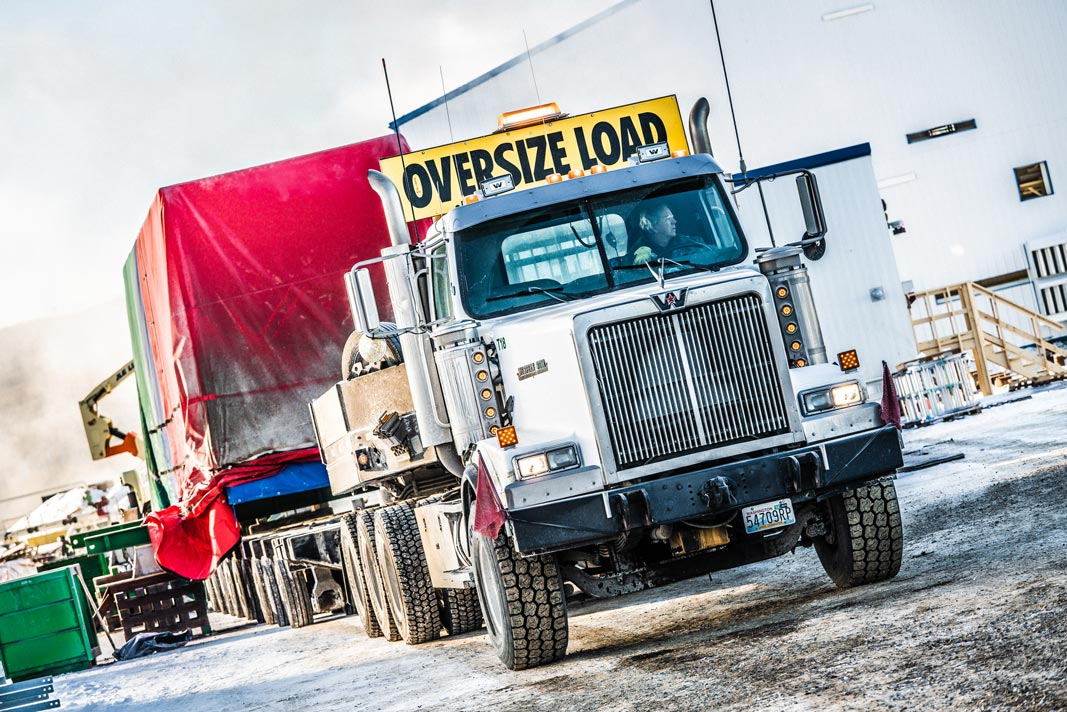 Omega Morgan specialized transport semi truck carrying an oversize compressor package load
