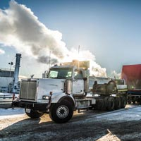 selected thumbnail button of Omega Morgan specialized transport semi truck carrying an oversize compressor package load in front of a bright sky with billowy clouds