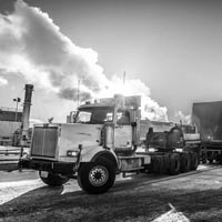 deselected thumbnail button of Omega Morgan specialized transport semi truck carrying an oversize compressor package load in front of a bright sky with billowy clouds