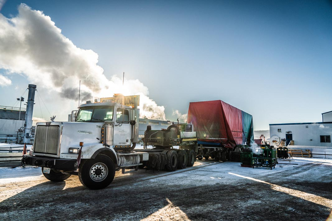 Omega Morgan specialized transport semi truck carrying an oversize compressor package load in front of a bright sky with billowy clouds