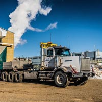 selected thumbnail button of Omega Morgan specialized transport semi truck carrying an oversize compressor package backed up to a building for offloading in Calgary