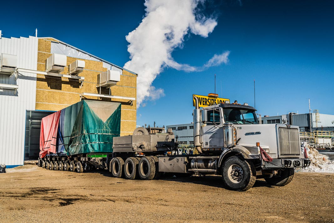 Omega Morgan specialized transport semi truck carrying an oversize compressor package backed up to a building for offloading in Calgary