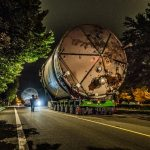 Omega Morgan Specialized transportation team transporting a twenty two foot wide ozone tank down a narrow road with trees on either side