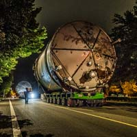 selected thumbnail button of Omega Morgan Specialized transportation team transporting a twenty two foot wide ozone tank down a narrow road with trees on either side