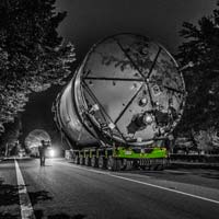 deselected thumbnail button of Omega Morgan Specialized transportation team transporting a twenty two foot wide ozone tank down a narrow road with trees on either side