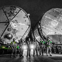 deselected thumbnail button of illuminated by headlights and streetlights, six Omega Morgan specialized transportation crew members stand in front of two ozone tanks on trailers for transport