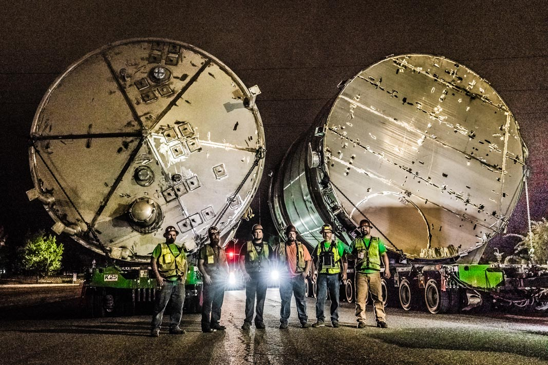 illuminated by headlights and streetlights, six Omega Morgan specialized transportation crew members stand in front of two ozone tanks on trailers for transport