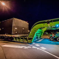 full color thumbnail of compressor package on a 150-ton dual lane trailer on the road at night