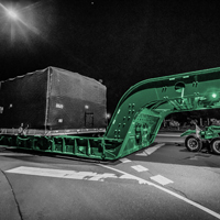 black and white and green thumbnail of compressor package on a 150-ton dual lane trailer on the road at night