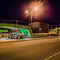 full color thumbnail of 150-ton dual lane trailer carrying compressor package on highway at night