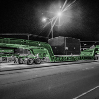 black and white and green thumbnail of 150-ton dual lane trailer carrying compressor package on highway at night