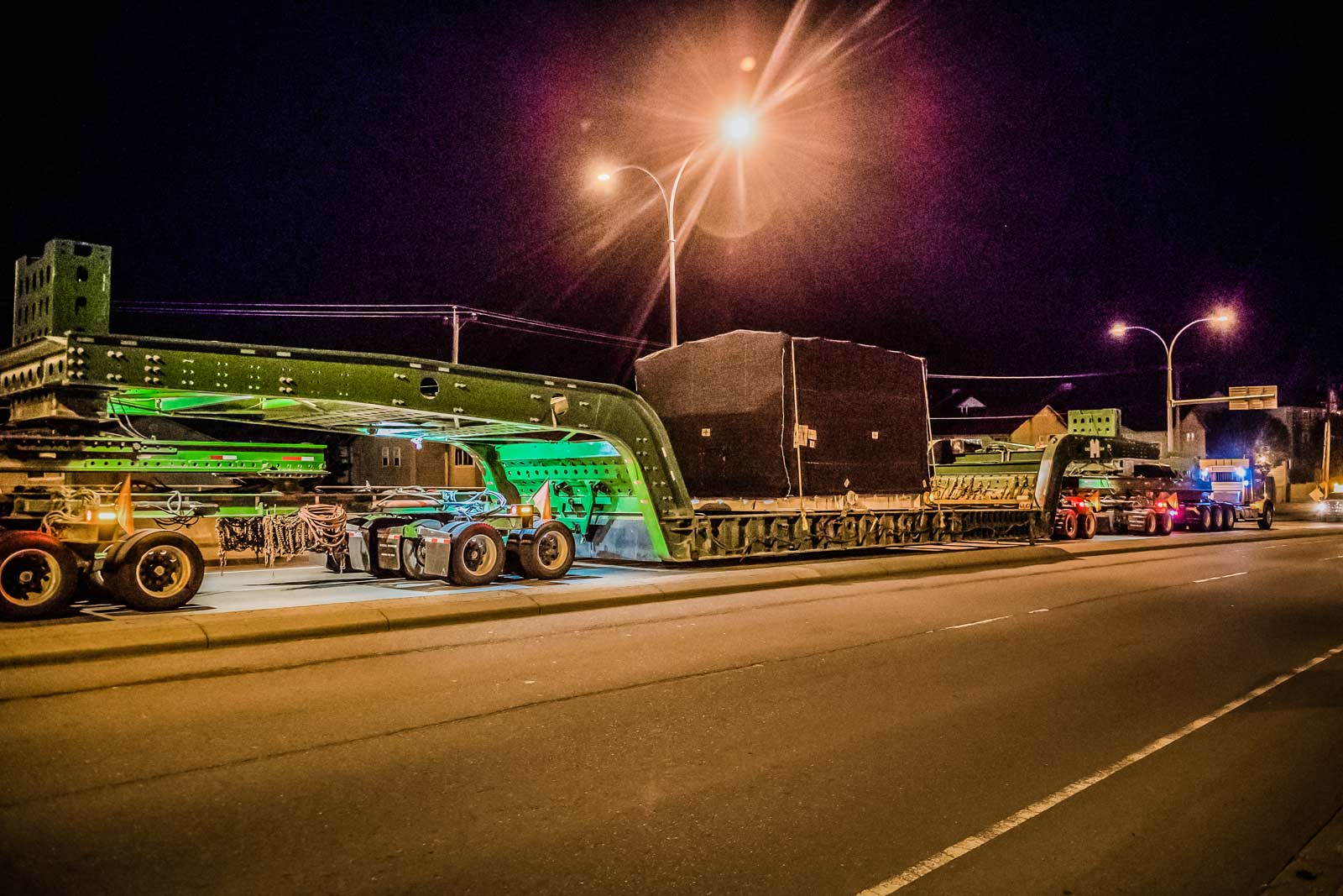 150-ton dual lane trailer carrying compressor package on highway at night