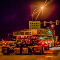 full color thumbnail of omega morgan 150-ton dual lane trailer carrying compressor package in british columbia at night with crew member standing beside trailer