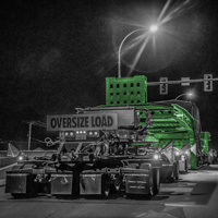 black and white and green thumbnail of omega morgan 150-ton dual lane trailer carrying compressor package in british columbia at night with crew member standing beside trailer