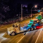 150-ton dual lane trailer carrying a compressor package turning on a road in British Columbia at night