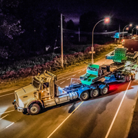 full color thumbnail of 150-ton dual lane trailer carrying a compressor package turning on a road in British Columbia at night